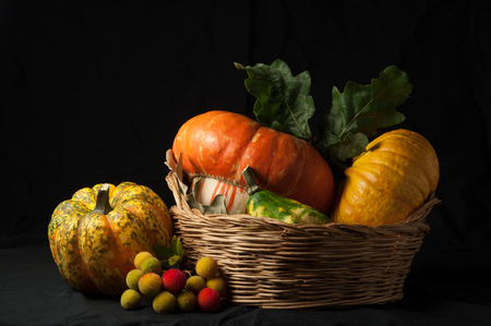 A group of pumpkins, placed in a wicker basket,  with a black background and a grazing light. Inspired to Renaissance still life paintings.