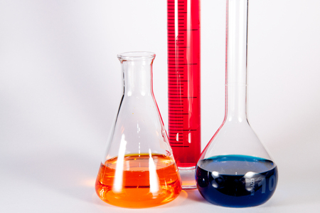 volumetric flask: Picture showing some chemistry lab glassware: from left to right an Erlenmeyer flask with a yellow liquid, a graduated cylinder with a magenta liquid, in volumetric flask with blue liquid.