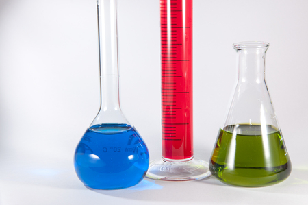 volumetric flask: Picture showing some chemistry lab glassware: from left to right in volumetric flask with blue liquid, a graduated cylinder with a magenta liquid, an Erlenmeyer flask with a green liquid.