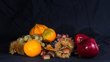 Group of autumnal fruits and vegetables on a black background.