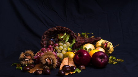 horn of plenty: A group of autumnal fruits and vegetables on a black background, with a cornucopia horn of plenty made of wicker