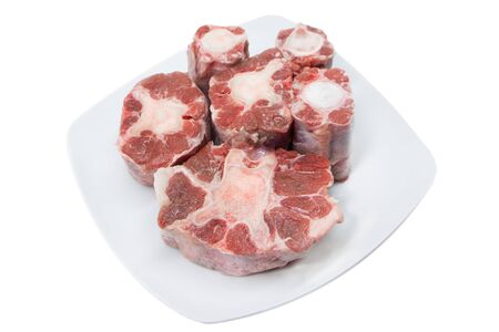 Six pieces of raw rabo de toro or bulls tail isolated on a white square plate on white background 免版税图像