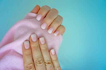 Stylish beautiful manicure. Pink and white light gradient ombre with a pink sweater on blue background. Banco de Imagens