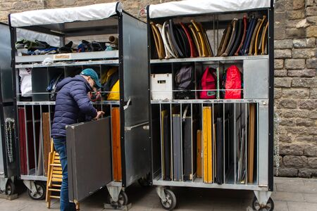 Street artist is removing his grey easel and putting it in a storage with many other easels and suitcases of other street artists. Tools, chairs and paintings storage.
