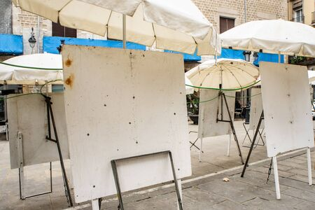 Empty dirty metal white easels on the street under white umbrellas. Street artists are gone for weekend. Selll paintings in the streets.