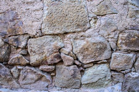 A texture of an old grey stone wall with concrete and big and small stones