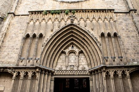 An entrance to the church as an element of gothic archetecture in Spain, Barcelona. Old ancient bas lica made of stone opened from outside