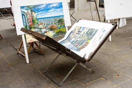 Opened easel briefcase with work of a street artist inside. Exhibition where painters sell their paintings. Stockfoto