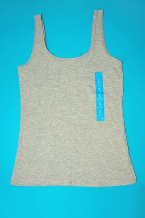 A flatlay top view of a casual gray female sleeveless top tank of a small size on blue background Stock Photo