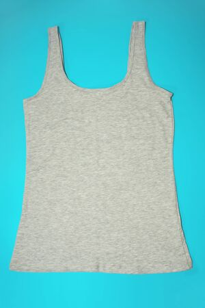 Gray sleeveless female casual tank top on blue background. Sport, fitness aparrel. Basic look.