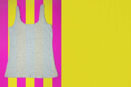 Gray sleeveless female casual tank top on bright striped yellow and pink background. Copyspace. Sport, fitness aparrel. Basic look. Stockfoto - 128780993