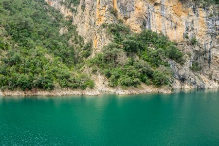 Grey and yellow cracked mountain rock with diagonal green plants and trees in a natural park congost de Mont-rebei Monrebey in Spain on the shore of a blue aquamarine river reflecting gorge.