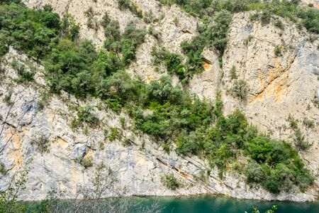 Cracked rock with green plants and trees in a natural park congost de Mont-rebei Monrebey in Spain with blue river, gorge and mountain