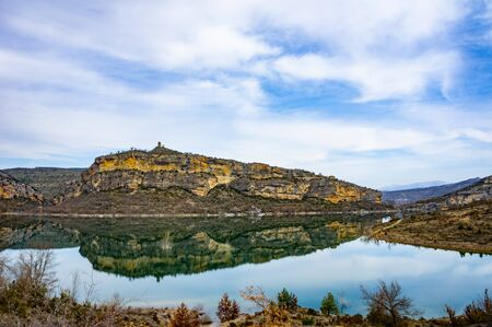 Grey and yellow beautiful mountain cliff in a natural park congost de Mont-rebei Monrebey in Spain on the shore of a blue river reflecting gorge. Stock Photo