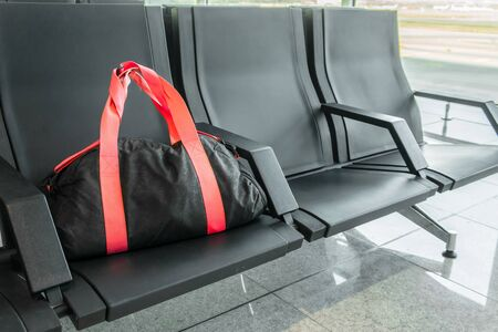Suspicious black sport bag left on chairs unattended. Lost luggage. Concept of safety in public places and terrorism