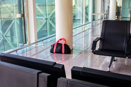 Suspicious black sport bag from luggage left unattended in the terminal of the airport. Concept of terrorism and public safety. Stock Photo