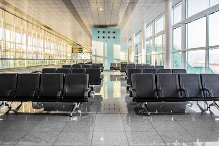 Several rows of modern black seats in the empty sunny waiting hall of the airport. Concept of loneliness, waiting, travelling, early flight, less people, crisis. Number of tourists decreases and falls..