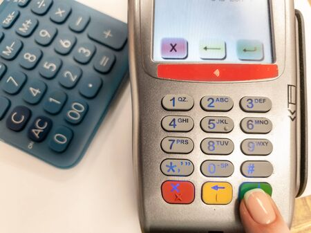 Woman pressing green button on a silver payment machine. Closeup of bank payment terminal. Processing NFC payment device. Top view. Blue calculator on white background. Concept of accepting the payment, easy payment, online transactions. Stock Photo