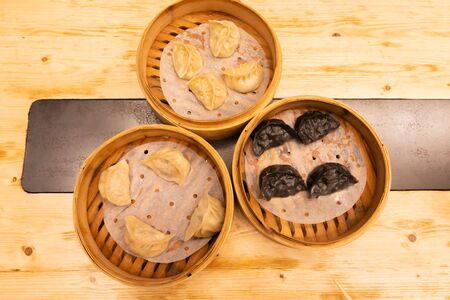 White meat, shrimps and mushroom steamed dumplings on a wooden table in a wooden steamer in an asian restaurant or chinese bar with dumplings. Flat lay. Top view.