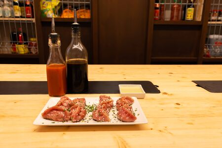 Two bottles of soy sauce and hot chili with red meat, shrimps and mushroom dumplings on a wooden table in an asian restaurant or chinese bar with dumplings