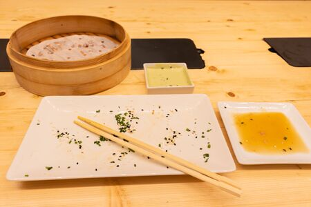 Empty plates and wooden steamer from steamed dumplings on a wooden table with chopsticks in an asian restaurant or chinese bar with dumplings. Stock Photo