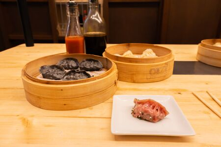 White, black and red pork meat, shrimps and mushroom steamed dumplings on a wooden table in a wooden steamer in an asian restaurant or chinese bar with dumplings. Two bottles on the nackground of soy  스톡 콘텐츠