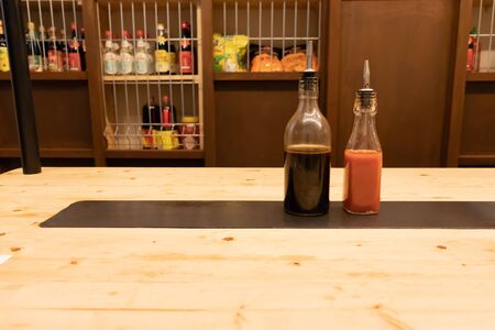 Two bottles of soy sauce and hot chili on a wooden table in an asian restaurant or chinese bar with dumplings 스톡 콘텐츠
