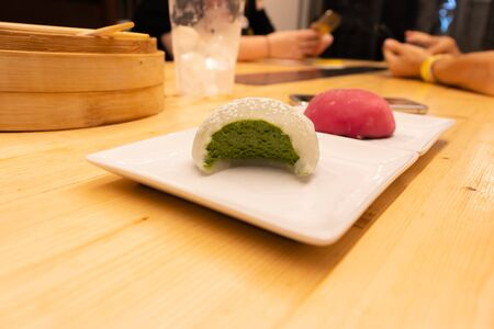Green tea biten and red raspberry big mochi on a plate on a wooden table in an asian restaurant or chinese dumplings. bar. Green creamy filling inside