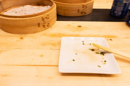 Empty plates and wooden steamer from steamed dumplings on a wooden table with chopsticks in an asian restaurant or chinese bar with dumplings. Finished eating. Stock Photo