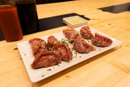 Two bottles of soy sauce and hot chili with red meat, shrimps and mushroom dumplings on a wooden table in an asian restaurant or chinese bar with dumplings.