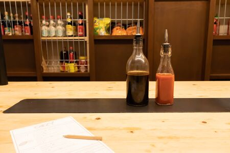 Two bottles of soy sauce and hot chili on a wooden table in an asian restaurant or chinese bar with dumplings Oizy in Barcelona Stock Photo