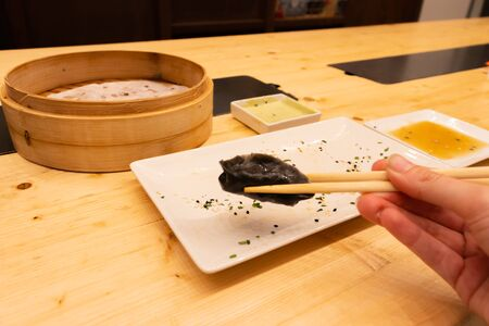 Man eating black pork meat, shrimps and mushroom steamed dumplings on a wooden table with chopsticks in an asian restaurant or chinese bar with dumplings.