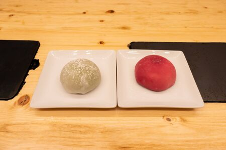 Green tea and red raspberry big mochi on a plate on a wooden table in an asian restaurant or chinese dumplings. bar Stock Photo