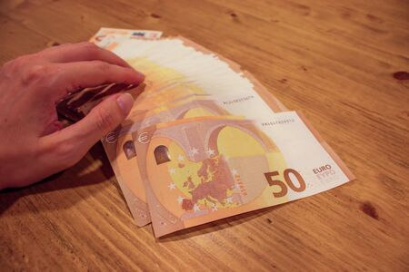 Female woman hand holding many 50 euro banknotes on a wooden table