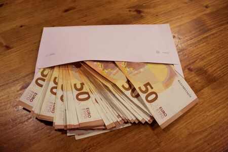 Bribe and tax concept. 50 euro banknotes falling out of the white envelope