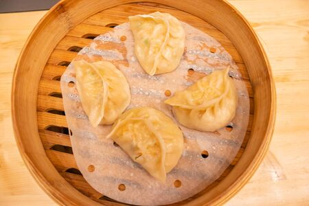 White meat, shrimps and mushroom steamed dumplings on a wooden table in a wooden steamer in an asian restaurant or chinese bar with dumplings.