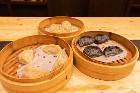 Red and White meat, shrimps and mushroom steamed dumplings on a wooden table in a wooden steamer in an asian restaurant or chinese bar with dumplings. Stock Photo