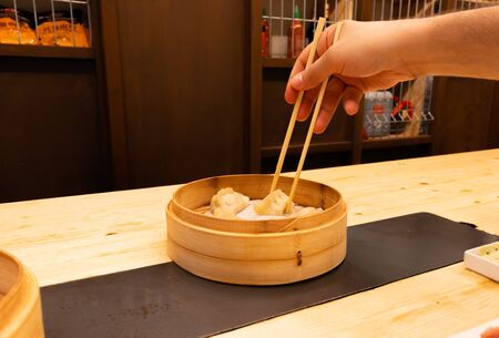 Man eating White, black and red pork meat, shrimps and mushroom steamed dumplings on a wooden table with chopsticks in an asian restaurant or chinese bar with dumplings.