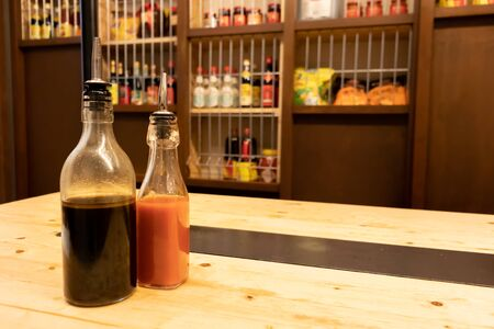 Two bottles of soy sauce and hot chili on a wooden table in an asian restaurant or chinese bar with dumplings Oizy in Barcelona 스톡 콘텐츠