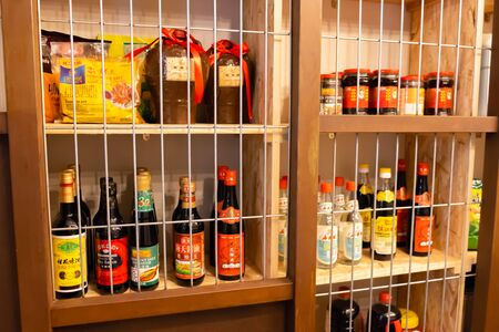 Big choice of various soy sauces in glass botlles and jars on wooden shelves Stock Photo