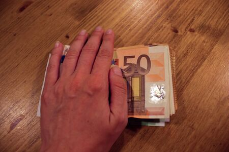 A closeup of a female caucasian woman hand covering a bunch of 50 euro bills. Stock fotó