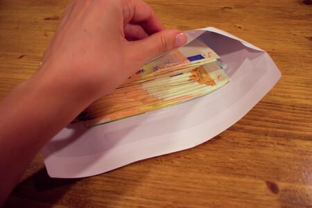 Female hand opening an envelope with money. 50 euro bills bribe.