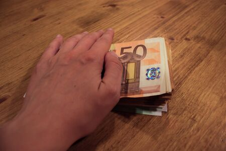 A female caucasian woman holding a hand of a stack of 50 euro banknotes. Bribes and taxes. 写真素材