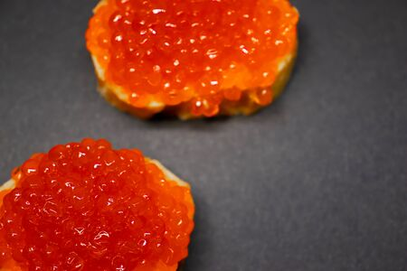 Two red salmon caviar canape close up on white baguette. Delishious russian dishes