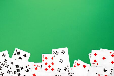 Deck of playing cards on green background table copy space