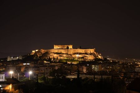 Night view of acropolis building on a hill with lights and beautiful scenery in Athens Greece