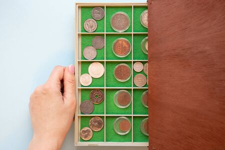 Numismatics. Caucasian woman hand takes out a plastic case from a wooden box full of different old rare expensive antique coins. Reklamní fotografie