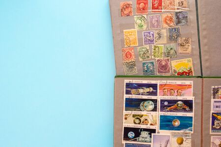 Stamp collecting. Two albums with old expensive valuable post stamps on blue background. Reklamní fotografie