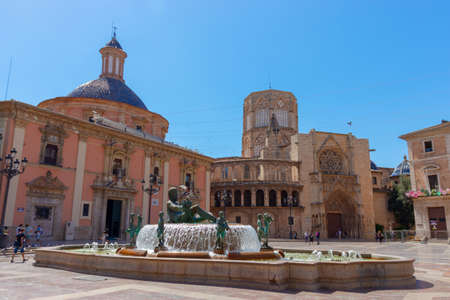 VALENCIA, SPAIN - JULY 15, 2020: Square with a fountain in front of Gothic Valencia Cathedral