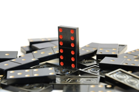 The scattered dominoes; only one to stand; a white background Stock Photo - 11658398